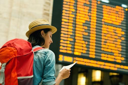 woman checking train time board
