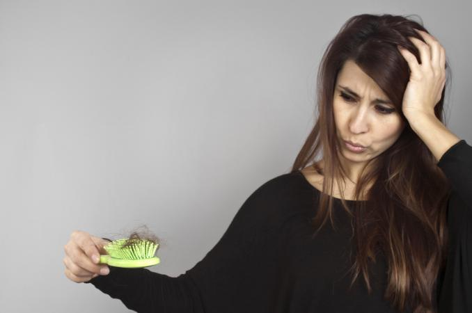 Woman holding hairbrush full of hair