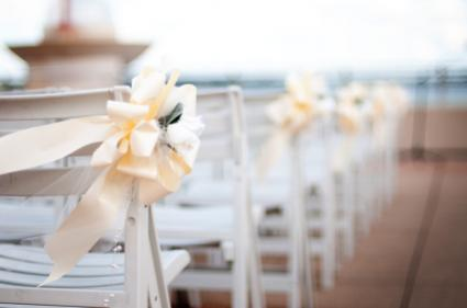 White chairs with yellow bows at a wedding