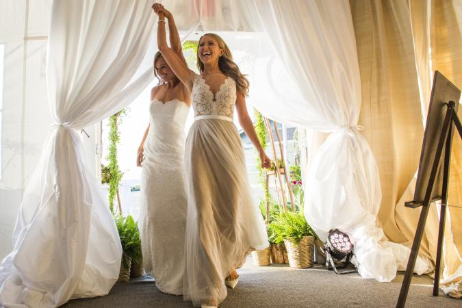 Brides walking through curtain
