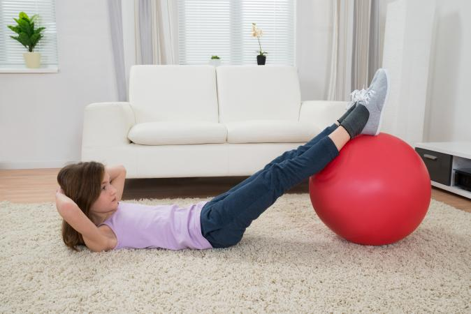 girl doing crunches with a yoga ball