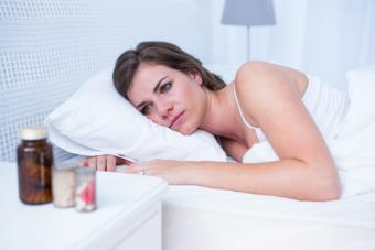 Sad woman looking at pills; © Wavebreakmedia Ltd | Dreamstime.com