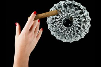 Female hand with cigar and ashtray