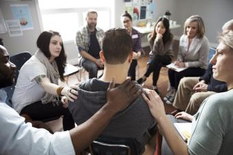 People comforting man in support at support group in community center