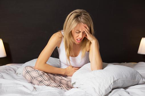 Woman with stomach cramps and headache