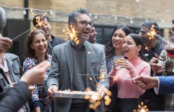 Amigos celebrando el cumpleaños con pastel y bengalas