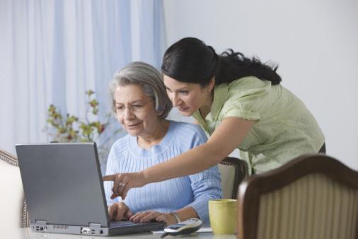 Adulto mayor e hija en la computadora