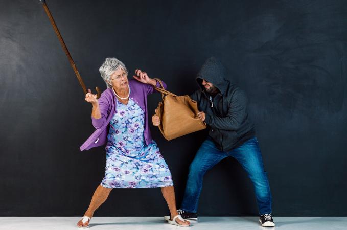 Mujer mayor defendiéndose contra atacante