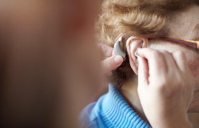 Mujer colocandose auriculares para la sordera