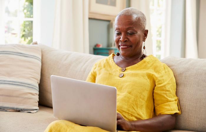 mujer mayor en el sofá usando su laptop