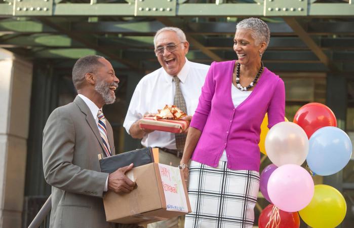 Compañeros de trabajo celebrando con un hombre jubilado