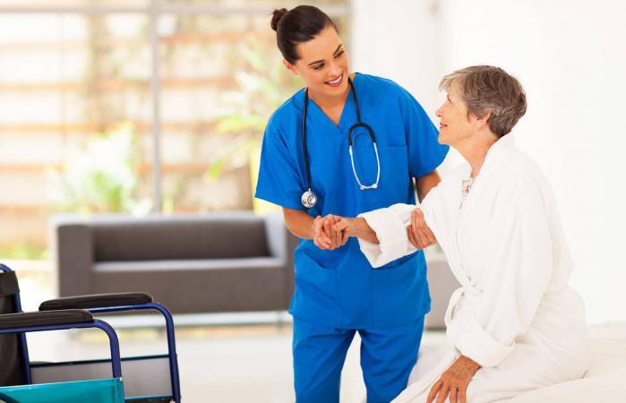 Enfermera ayudando a una mujer mayor