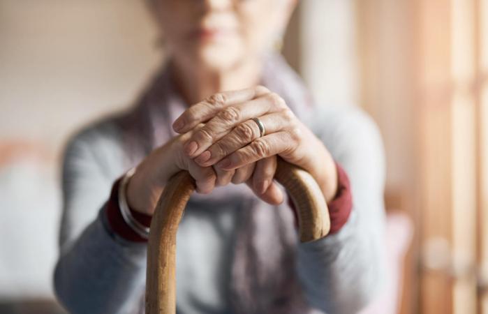 mujer mayor sosteniendo un bastón