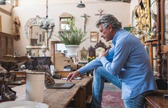 owner of antique store using laptop
