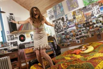 Teen girl dancing in her bedroom full of photos and posters