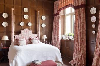 Bedroom with wooden wall panelling and decorative china plates