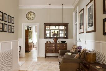 Antique wooden drawers and mirror in hallway with leather armchairs and vintage trunks