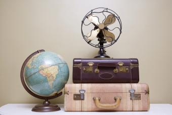 Retro items including two suitcases, a globe and a fan that sit on a white table