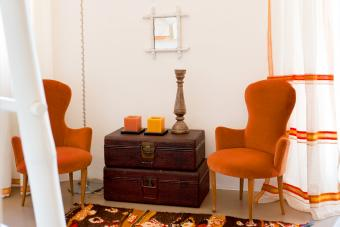Italian chairs flank vintage trunks in room with Moroccan rug