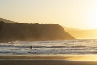 Surfer carrying surfboard into the ocean