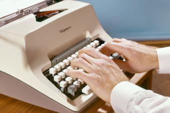 Man writing on Olympia Manual Typewriter