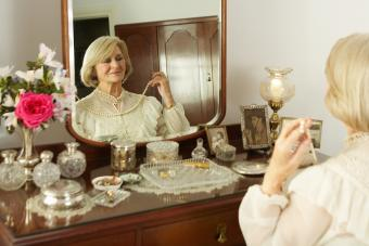 Senior woman sitting at vanity set, trying on necklace