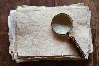 A stack of sheets of recycled paper lying on a wooden table and an antique hand held magnifier glass
