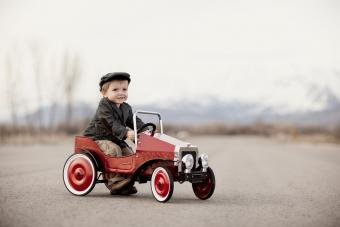 A young boy driver is out for a drive in his pedal car.