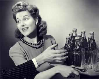 1950s woman carrying tray of drinking glasses & soda