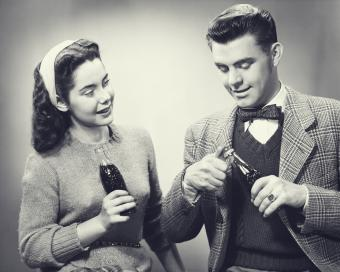 Young couple holding bottles of cola in studio