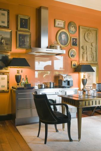 'Hermes' orange walls and closely grouped pictures in kitchen with Gaggenau appliances