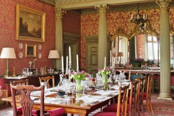 Laid table in large dining room with red and gold design wallpaper