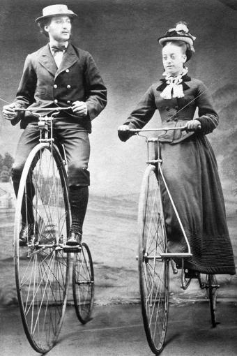 Lady and gentleman riding ordinary bicycles with Starley wheels, 1874