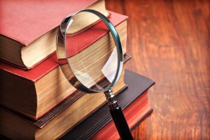 Examining antique books; copyright Flynt at Dreamstime.com