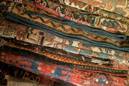 A stack of, handmade colorful knotted antique Persian oriental rugs made of wool.