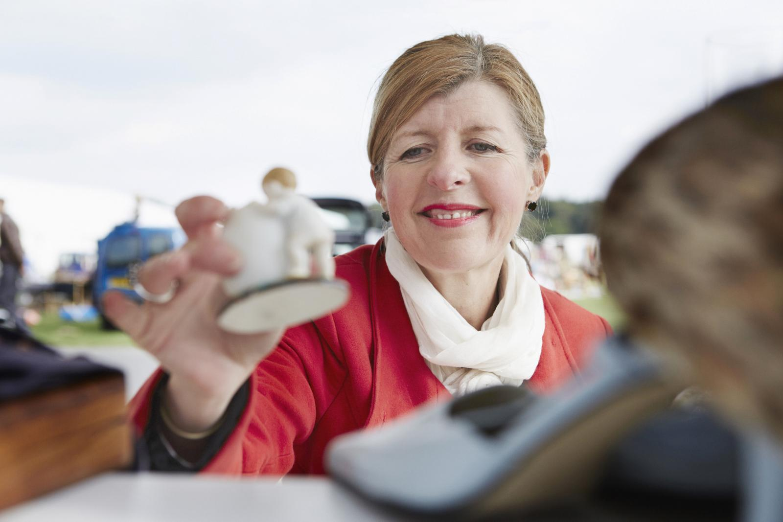 Woman in a red coat holding a vintage porcelain figurine at a flea market