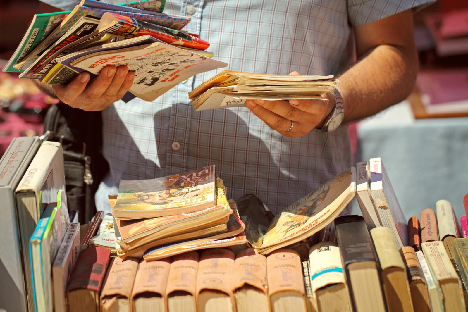 Man Holding Books At Flea Market