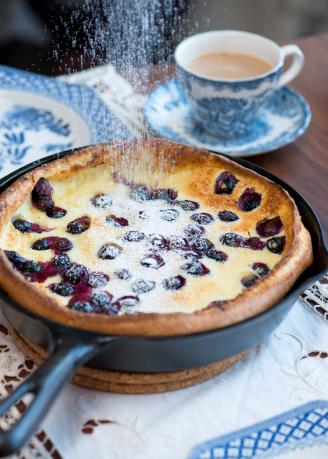 Dusting sugar on fresh blueberry tart on antique cast iron pan and blue china