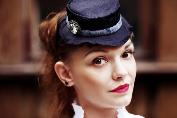 Beautiful red hair woman in vintage clothes and hat with hatpin