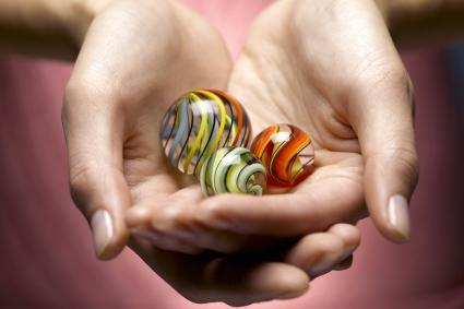 Young woman holding glass marbles in cupped hands