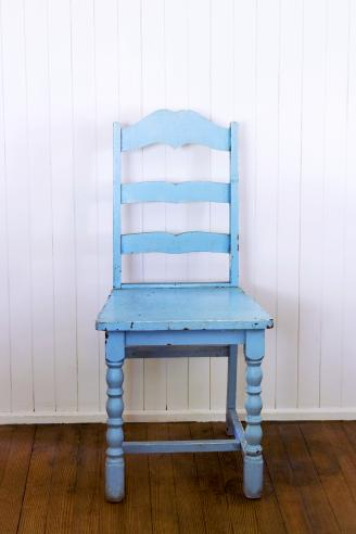 Old Blue Ladder Back Chair Against White Wall