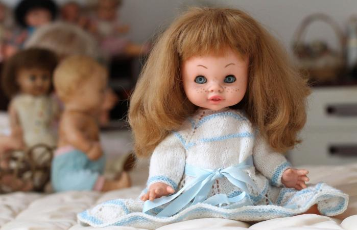Vintage doll sitting in bed