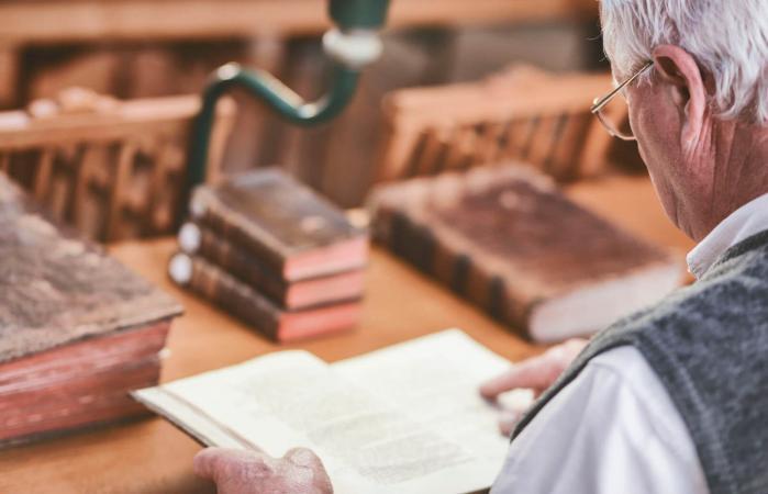 Senior man looking at antique books
