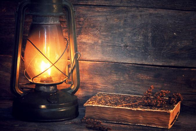 Illuminated Antique Lantern With Old Book On Table