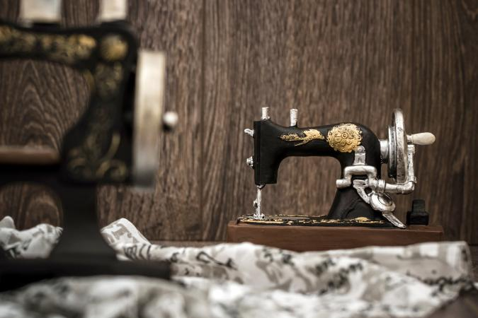 Small nostalgic decorative sewing machine on brown wooden background