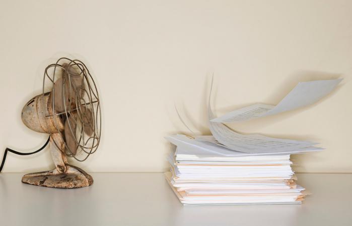 Electric fan blowing on heap of papers