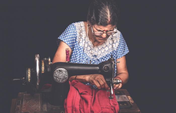 woman sewing clothes with sewing machine