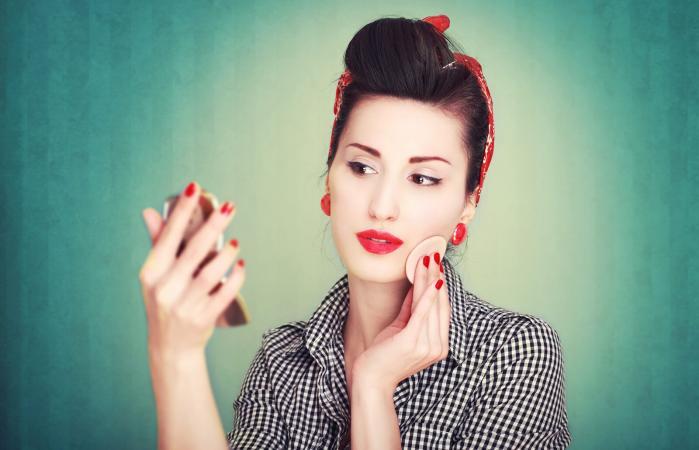 Vintage woman applying makeup