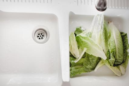 Water washing lettuce in a farmhouse sink