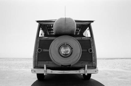 Old Woodie station wagon with surfboard at the beach